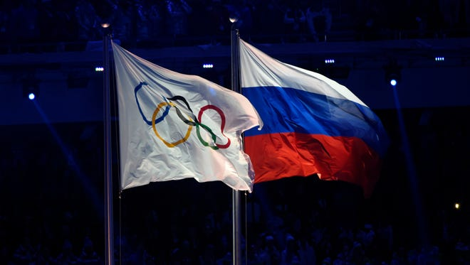 The Olympic flag (left) flies next to the Russian  flag during the opening ceremony for the Sochi 2014 Olympic Winter Games.