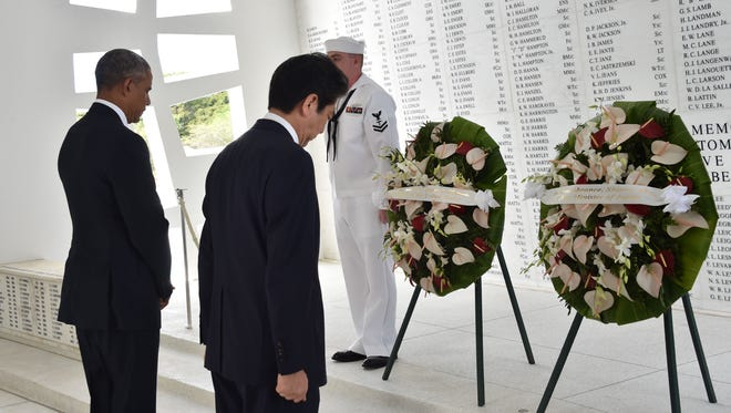 President Obama and Japanese Prime Minister Shinzo Abe place wreaths at the USS Arizona Memorial.
