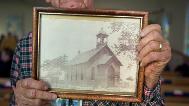Ken Johnson, a church elder, holds a framed photograph of the First Presbyterian Church of Peoria's original building, circa 1900, before worship services at the church on Sunday, Jan. 22, 2017. The church is the oldest in Peoria, dating back to at least 1900.