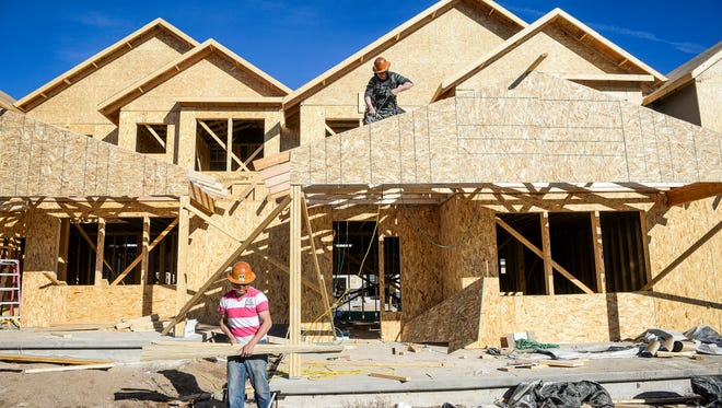 Francisco Rios, left, and Plinio Santin work on framing at the Bucking Horse Townhome project in Fort Collins in early 2015.