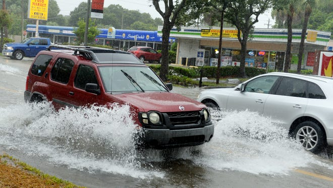 Motorists contend with flooding on 21st Street in August between 10th and 11th avenues in Vero Beach. A low-pressure system entering the Treasure Coast on Wednesday could cause motorists to see ponding and flash flooding in low-lying areas.