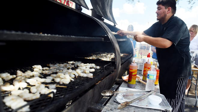 Leo Mendez, with Woody's Bar-B-Q, puts another batch of shrimp on the grill, Feb. 25, 2017, on the first day of the ShrimpFest & Craft Brew Hullabaloo in Fellsmere.