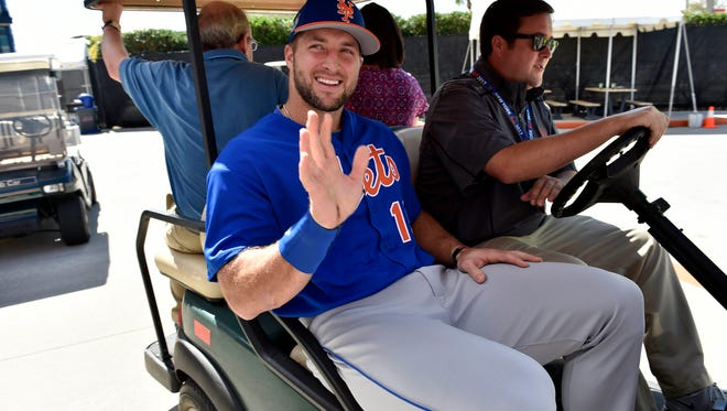 Tim Tebow is seen leaving on a golf cart after addressing members of the media.