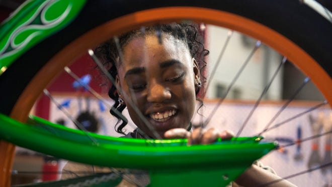 Jamesha Fain works on a bike at DreamBikes on North Central Street Tuesday, Feb. 28, 2017. DreamBikes is a local nonprofit that strategically places used bicycle stores in low-to-moderate income neighborhoods to provide hands-on paid job training to teens.