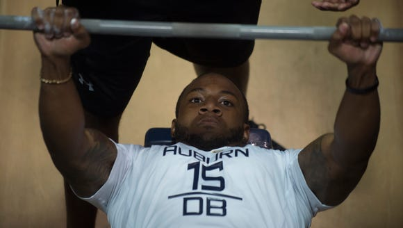Auburn defensive back Joshua Holsey (15) bench presses