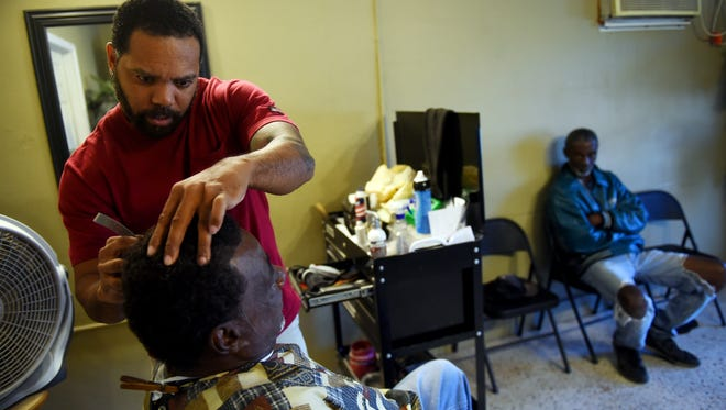 """Local barber Duane Turner gives a haircut to Earl Jackson as he talks with friend James Austin (right) on Wednesday, March 29, 2017, at Kool Kuts barbershop on Old Dixie Highway near Gifford. In the wake of the shooting deaths of Indian River County Sheriff's Deputy Garry Chambliss and Alteria Woods, who died during an early-morning raid by law enforcement, members of the Gifford community seek out places like the barbershop to talk about the events happening in their community. """"Change begins in the home,"""" Turner said. """"It doesn't happen out in the streets, but in the home."""""""