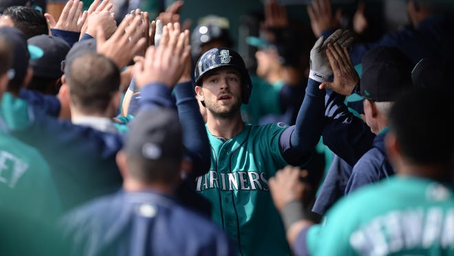 Mariners rookie outfielder Mitch Haniger (center) high-fives teammates after hitting a home run this spring.