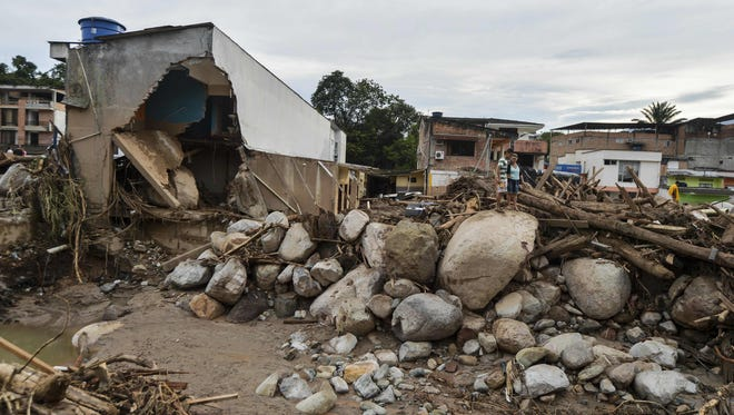 People look at damage caused by slides following heavy rains in Mocoa, Putumayo department, southern Colombia on April 2, 2017.  The death toll from a devastating landslide in the Colombian town of Mocoa stood at around 200 on Sunday as rescuers clawed through piles of muck and debris in search of survivors.