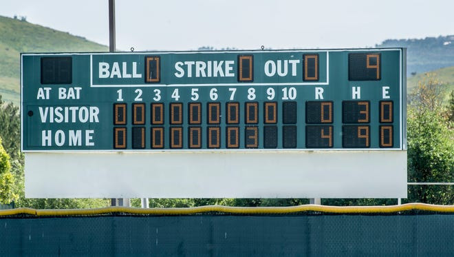 A baseball scoreboard is lit up to reflect the score of a game.