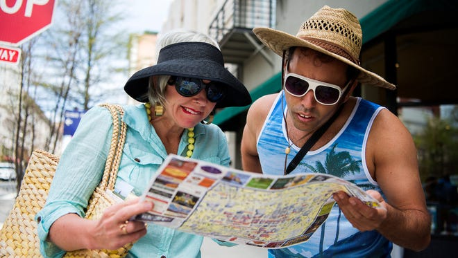 LaZoom owners Jen and Jim Lauzon, acting as lost tourists, look at a map of Asheville on Haywood Street in downtown.