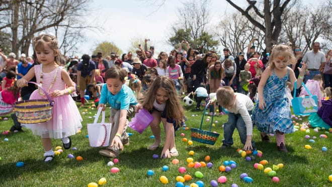 Kids storm the a field of eggs during an Easter egg hunt hosted by Antioch Community Church in City Park on Saturday, April 15, 2017. Festivities included carnival games and bounce houses.