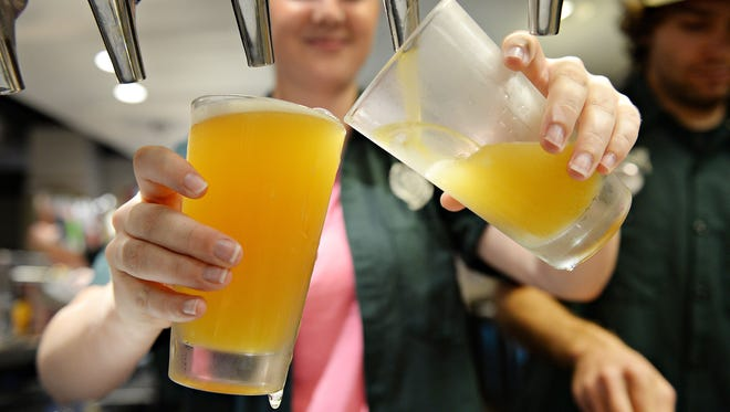Audrey Meyer pours beers at CSU's Ramskeller at the Lory Student Center. Next year, the bar will serve beers mad eon campus by fermentation science majors.