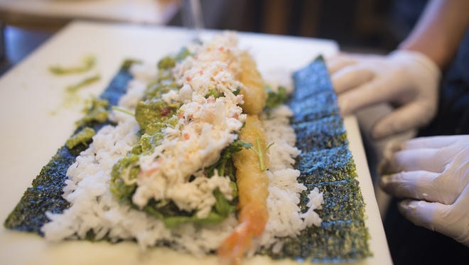 Micki Hudson, head chef at Wabi Sabi on Linden St. prepares a sushi burrito Tuesday, May 25, 2016. The item has become a staple to the Old Town restaurants lunch menu after the one-time item proved to be popular.