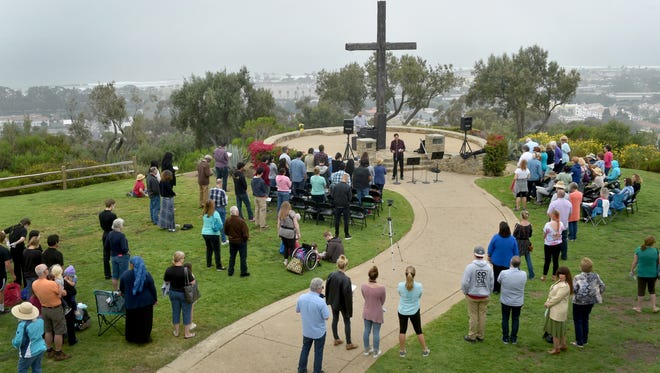 Nearly 100 people from more than a dozen area churches gather for a National Day of Prayer event at Serra Cross in Ventura on Thursday.