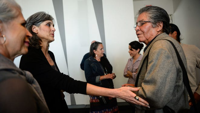 """Walker Art Center Executive Director Olga Viso touches the arm of Dakota elder Sheldon Wolfchild as they parted ways following a press conference with a group of Dakota tribal elders with officials from the Walker Art Center and the Minneapolis Park Board to discuss the controversial """"Scaffold"""" sculpture at the center, Wednesday, May 31, 2017, in Minneapolis. Officials of the Walker Art Center say Native American tribal leaders will oversee the dismantling beginning Friday of a gallows-like sculpture that reminded protesters of the mass hanging of 38 Dakota men in 1862."""