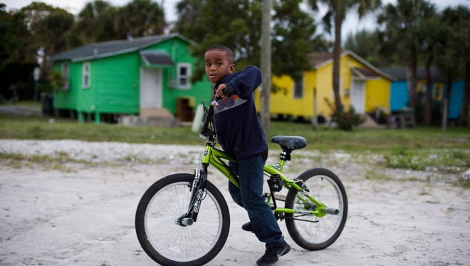 Claudius Taylor III, 6, pauses from a bike ride on his family's property to pose for a photo Jan. 12, 2016 in East Stuart. The homes will be demolished this summer after the city deemed them unsafe, said Ben Hogarth, city spokesman.