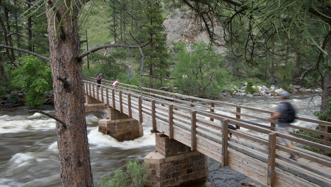 Hikers cross a bridge to reach the Grey Rock trailhead on Thursday, June 15, 2017. The river is flowing above 2,000 cubic feet per second at the mouth of Poudre Canyon.
