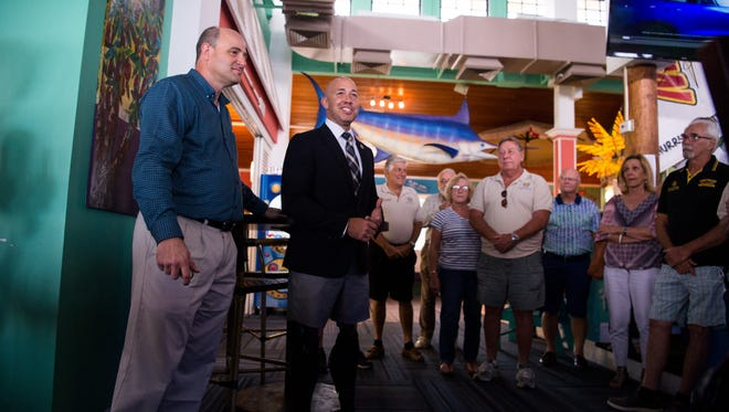 U.S. Rep. Brian Mast (center) and Stuart Mayor Troy McDonald attend a Vietnam Veterans of America, Chapter 1041, fundraiser Friday, July 21, 2017, at Mulligan's Beach House in Stuart, to pay for care packages to send to military troops serving in combat zones.
