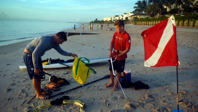 "Todd Rapp (left), and son Braden, of Vero Beach, prep their diving gear, Wednesday, July 26, 2017, as they get ready to enter the water south of Humiston Beach in Vero Beach on the first day of the lobster mini-season. ""This is the first time I've done this from a paddle board,"" Todd Rapp said. ""It should be a little easier than having to climb into a kayak."" To see more photos, visit TCPalm.com."