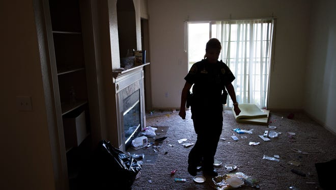 Larimer County Sheriff's Deputy Barb Bowman walks around a living room after tenant was evicted from a condo in south Fort Collins on Thursday, July 27, 2017. The Sheriff's Office assists with around 10 evictions a week around the county.