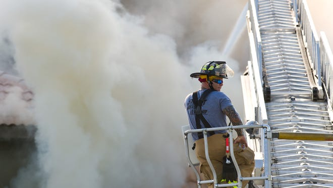 A firefighter helps extinguish the fire at the Nobile Shoes store, 888 Colorado Ave., that erupted July 27, 2016. Stuart and Martin County fire rescues worked to extinguish the fire even though the store was located in Stuart, according to county officials.