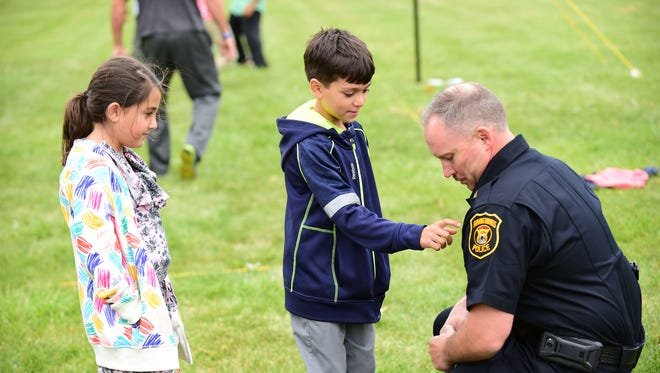Seema Sinan looks on as Amir Albakkour checks out Farmington Hills Police  Commander Jeff King's badge during the annual volleyball tournament.