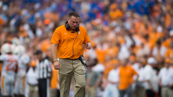 Vols coach Butch Jones walks toward an injured player on the field during the game against Florida on Sept. 16, 2017.