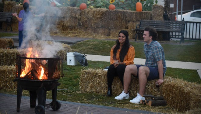 Farmington residents Roshni Shah and boyfriend Alex Sexton sit on hay bales and enjoy craft beer that was on hand at the annual Harvest Moon celebration in Farmington.