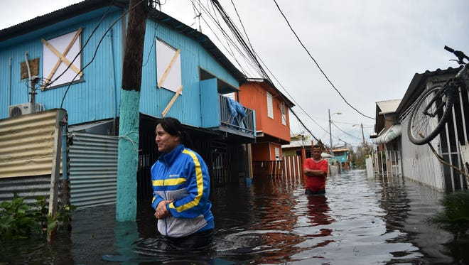 Residents cross a flooded street in Juana Matos, Puerto Rico, on Sept. 21 in the wake of Hurricane Maria. The entire island was left without electricity.