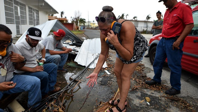 A woman tries to talk with her family to say that she is in good condition while telephone technicians try to repair the lines in Punta Santiago, Humacao, in the east of Puerto Rico, on Sept. 27, 2017, one week after the passage of Hurricane Maria.