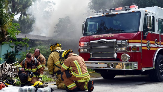 Indian River County Fire Rescue personnel replace their oxygen tanks after responding to a fire that started in a home in the 1600 block of 24th Avenue on Wednesday, Oct. 4, 2017, in Vero Beach. The house was unoccupied at the time of the fire. A representative of the state Fire Marshal's Office is coming in to determine the cause of the fire.