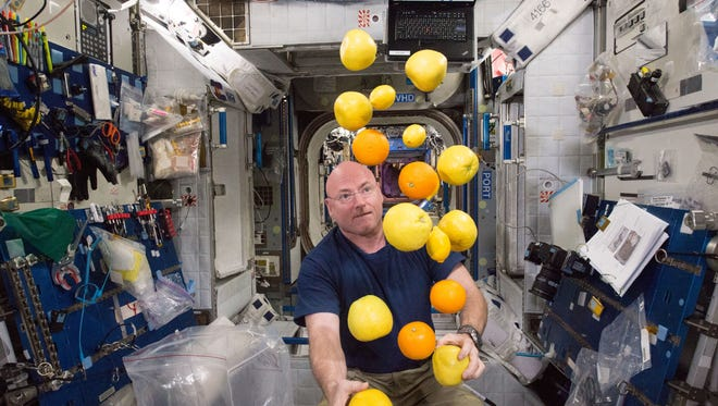 Astronaut Scott Kelly wrangles a recently delivered supply of fresh fruit about the International Space Station in 2015.