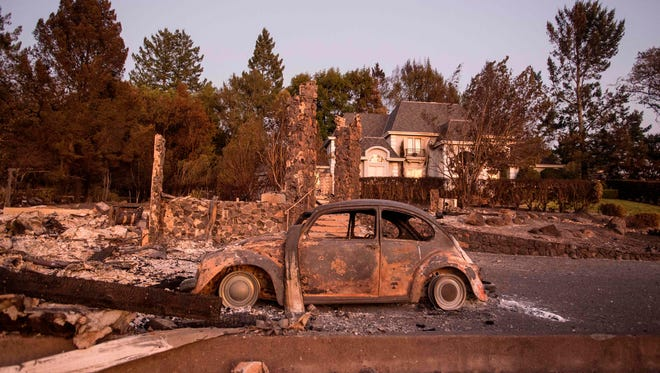 Charred property is seen before a home that was untouched by the fire in Santa Rosa, Calif. on Oct. 15, 2017. The death toll from California's wildfires rose to 40, Oct. 15, 2017, but firefighters reported progress in battling the flames, and thousands of evacuees were gradually being allowed to return home. The wealthiest US state regularly faces late-summer fires. But the blazes which have burned more than 217,500 acres (about 88,090 hectares) this month, and devastated the winemaking areas of Napa and Sonoma, proved the deadliest in the state's history. Almost 11,000 firefighters from various states are in action against the Calif. blazes.