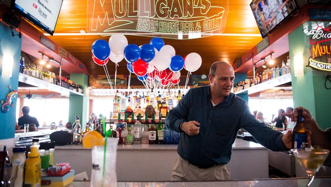 Stuart Mayor Troy McDonald serves behind the bar at the Vietnam Veterans of America, Chapter 1041 in Martin County, fundraiser Friday, July 21, 2017, at Mulligan's Beach House in Stuart. Mulligan's lease is one of three issues voters will decide in the upcoming special election.