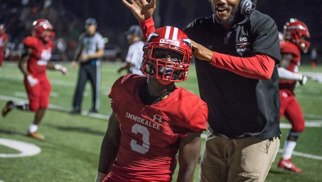 Shedro Louis celebrates after a touchdown with coach during the Class 5A regional semifinal game against Dunbar High School in Immokalee, Fla., on Friday, Nov. 17, 2017.