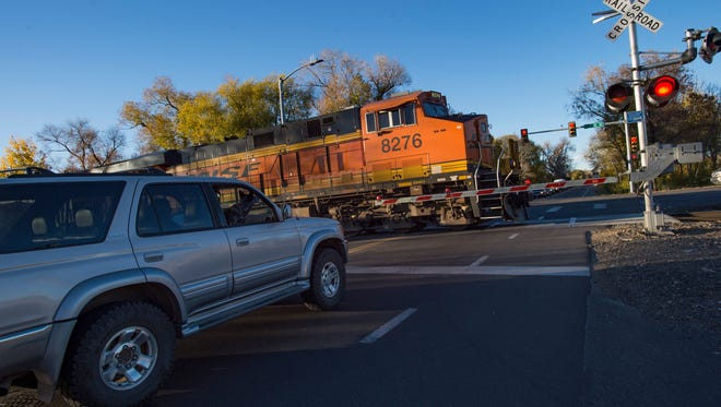Evening traffic waits to proceed northbound on Lemay Avenue as a train crosses Vine Drive in October.