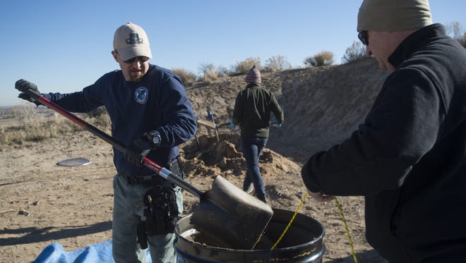 Northern Colorado Bomb Squad Commander Sgt. Ryan Ertman of the Loveland Police Department adds sand to a barrel holding a device while Fort Collins Police Services Officer Todd Hopkins holds a blast cord on a range west of Fort Collins on Tuesday, Dec. 5, 2017. The Northern Colorado Bomb Squad is working with Alex Smyth, a researcher from the United Kingdom, on testing a device that would aid with explosives investigations.