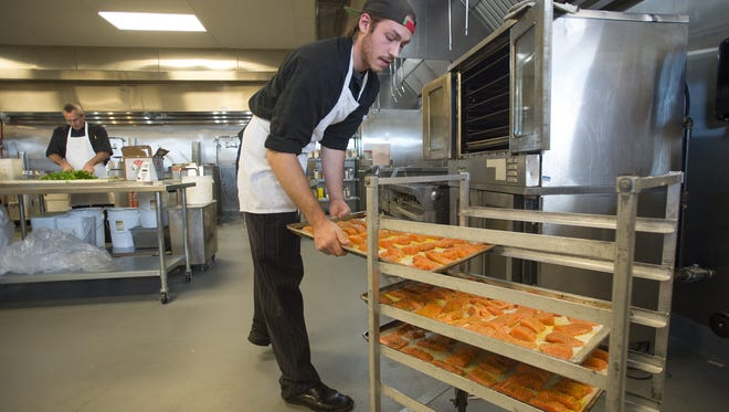Peter Rosis tosses pans of salmon filets in the oven at Spoons on Friday, December 7, 2017.