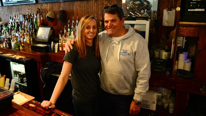 Woody's Bartender Kasey O'Brien and Jimmy O'Conor, Owner, pose for a photo on Tuesday, Dec. 12, 2017.