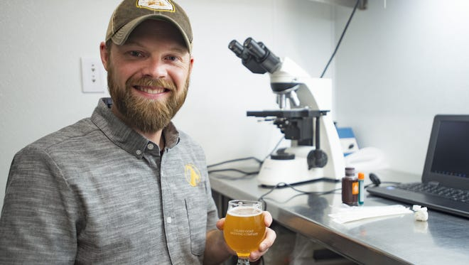 Charlie Hoxmeier poses for a photo in the lab at Gilded Goat Brewing Co. in Fort Collins on Wednesday, December 13, 2017. The brewery has invested in quality control through various testing methods in the brewing process.