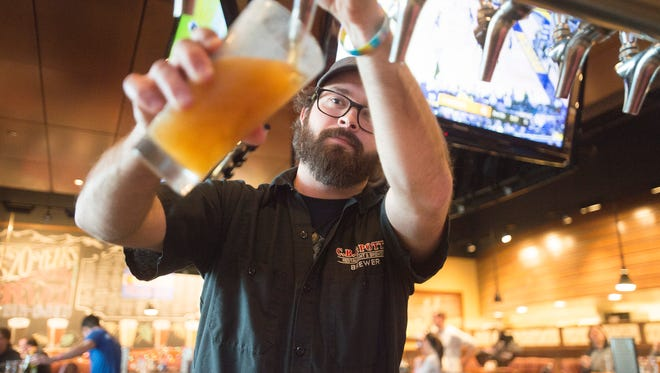 Head Brewer Jeff Eaton pours a pint of beer from the bar at C.B. & Potts on Foothills Parkway on Thursday. C.B. & Potts is planning a new brewery and taproom on Mulberry Street in 2018.
