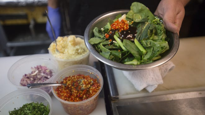 Spices are added to a dish of Chinese broccoli at Cafe de Bangkok on Friday, January 5, 2018. The popular Thai restaurant in Campus West has a selective hiring process to ensure cooks have proper training.