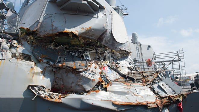 In this released U.S. Navy handout, the Arleigh Burke-class guided-missile destroyer USS Fitzgerald (DDG 62) sits in Dry Dock 4 at Fleet Activities Yokosuka to continue repairs and assess damage sustained from its June 17 collision with a merchant vessel.