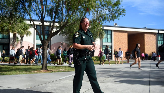 Indian River County Sheriff's Deputy Jessica Ogonoski shares a laugh with students between classes Tuesday, Feb. 6, 2018, at Vero Beach High School. Resource officers in the district have been reassigned to help the county during school closures.