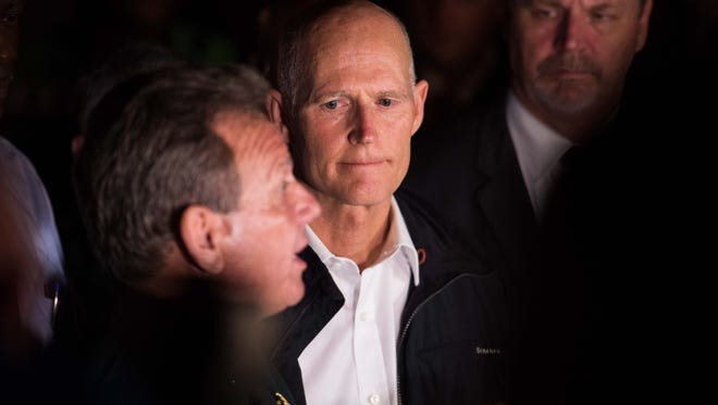 Florida Gov. Rick Scott listens to Broward County Sheriff Scott Israel speak at a news conference near Marjory Stoneman Douglas High School in Parkland on Wednesday, Feb. 14, 2018, following a mass shooting at the school.