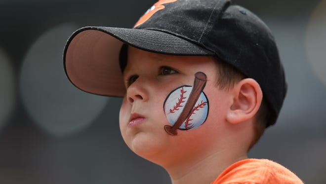 In this Aug. 6, 2017, file photo, a young baseball fan looks on before the Baltimore Orioles and Detroit Tigers baseball game, in Baltimore. The Orioles have launched a program that will enable kids to attend home games this season free of charge.
