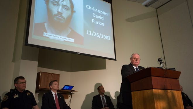 A mugshot of Christopher Parker is projected above Captain Bob Coleman of the Larimer County Sheriff's Office during a press conference updating the public on the Northern Colorado Shooting Task Force in Loveland on Thursday, March 15, 2018. Parker, 35, was arrested on suspicion of first-degree murder in the death of William Connole in 2015.