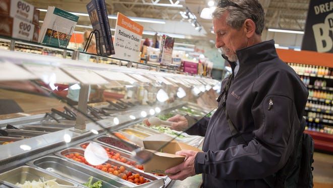 Larrey Kerling loads a bowl with salad at Whole Foods in Fort Collins on Friday, March 15, 2018. The grocery chain has been offering a salad bar and other prepared foods for quick meal options since it opened in 2004.
