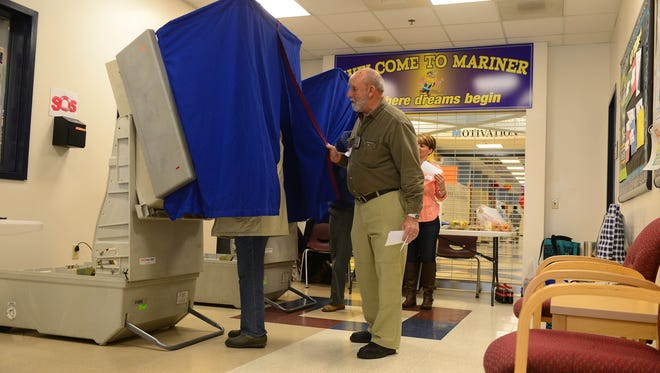 A polling attendee helps Cape Henlopen School District residents cast their vote for the Cape Henlopen referendum vote held on Tuesday, March 20, 2018 at Marnier Middle School in Milton, Del.