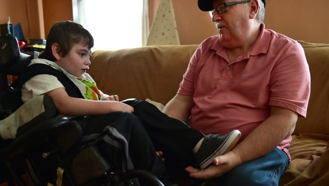 Robbie Elam, left, spends time with his father Bill Elam in their home after Robbie arrives home from school.